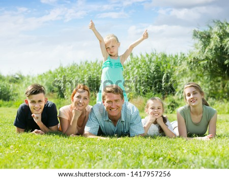 Portrait of happy large family of six lying together on green lawn outdoors #1417957256
