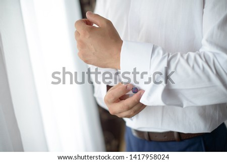 Young Caucasian male getting dressed in front of a window.  Horizontal detailed close-up shot of elegant male wearing white shirt and blue suit, getting ready, putting on a pair of vintage cuff links. #1417958024