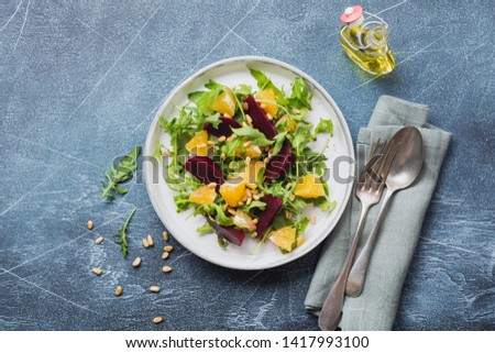 Beets, orange, pine nut, olive oil, feta cheese and arugula salad in ceramic plate on old concrete table background. Top view. #1417993100