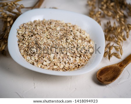 Oat flakes and ears of oats. Oatmeal in a plate on the table. Healthy breakfast #1418094923