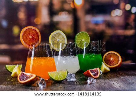 Tropical summer cocktails on a bar counter over restaurant lights background. Refreshing orange, white and green beverages. Copy space #1418114135