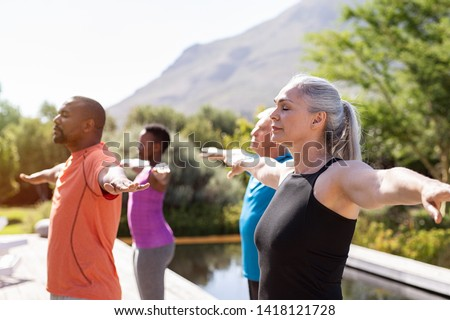Group of senior people with closed eyes stretching arms outdoor. Mature yoga class doing breathing exercise. Women and men doing breath exercise with outstretched arms. Balance and meditation concept. Royalty-Free Stock Photo #1418121728