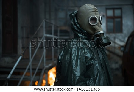 Scientist dosimetrist (radiation supervisor) in protective clothing and gas mask explores the danger zone. Fire. Close-up #1418131385