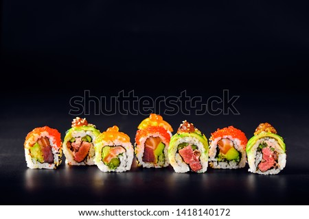 Close-up of uramaki sushi rolls with red caviar, salmon, tuna, cucumber and avocado isolated on black background. Delicious traditional japanese food with sushi rolls. #1418140172