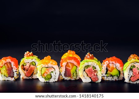 Close-up of uramaki sushi rolls with red caviar, salmon, tuna, cucumber and avocado isolated on black background. Delicious traditional japanese food with sushi rolls. #1418140175