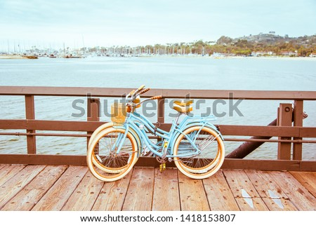 Two retro bicycles standing on Santa Barbara pier, California, USA. Vintage filter with muted teal blue and orange colors. Santa Barbara romantic concept on sea, beach, yacht club panorama background