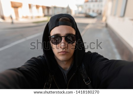 Attractive young hipster male in stylish cap in a trendy hoodie in trendy sunglasses makes a selfie on the phone near vintage buildings in the city on a sunny day. American guy. Modern street style. #1418180270