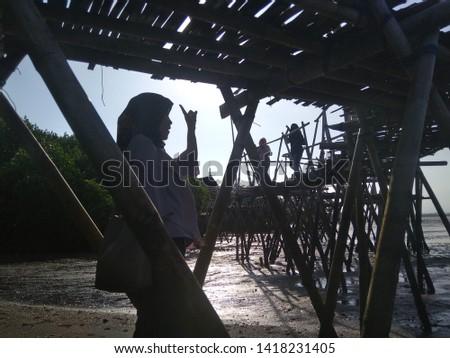 Banyuwangi, east Java / Indonesia - June 7 2019 : Local tourists are enjoying views of Cemara beach, the mangrove area of Blambangan peninsula. they fill the Eid holiday with visitin destination  #1418231405