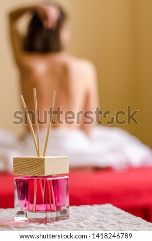 Aroma glass bottle scents for home perfumes raspberry color with bamboo sticks glass jar with wooden lid freshener on background of blurred naked woman's body #1418246789