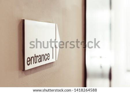 Entrance sign with direction arrow on the wall in modern building. #1418264588