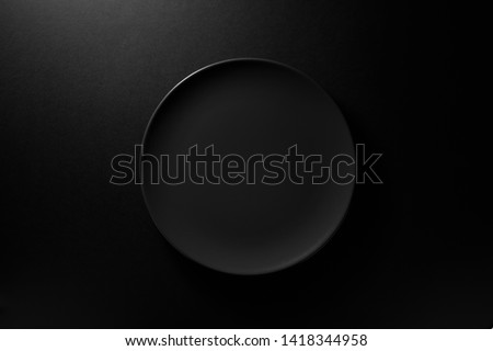 Empty round black plate on dark moody black background with copy space. Overhead view  #1418344958
