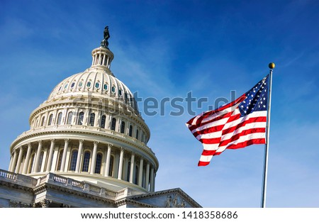 American flag waving with the Capitol Hill in the background Royalty-Free Stock Photo #1418358686