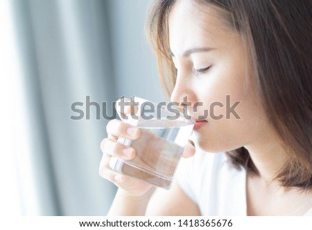 Close up woman drinking pure water from glass with light in the morning, Selective focus #1418365676