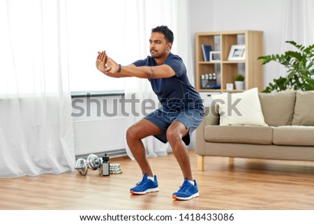 sport and healthy lifestyle concept - indian man with fitness tracker exercising and doing squats at home #1418433086