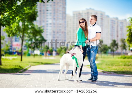 Happy couple with a dog having fun outdoors in the city #141851266