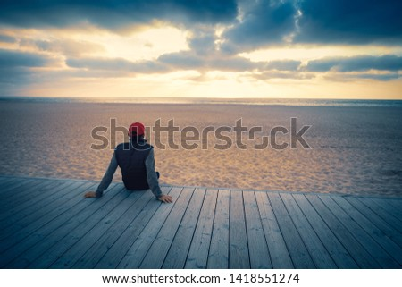 Silhouette of man on the beach looking at magical sunset. Man sitting on the wooden terrace #1418551274