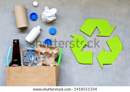 Recycling symbol and different garbage on gray background. Top view. #1418551334