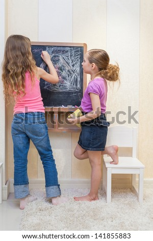 Two little girls in the playroom paint on the blackboard