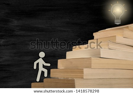 The man figure stepping books. reaching the target by reading. concept photo