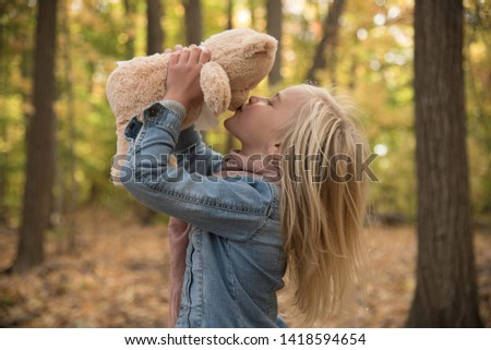 Young blond female child kissing her stuffed teddy bear in autumn