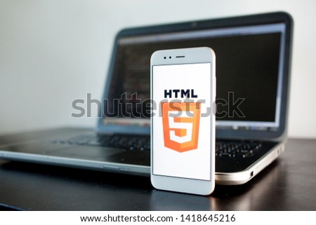 SAINT PETERSBURG, RUSSIA - MAY 16, 2019: Mobile application development, HTML5 programming language for mobile development. Workplace of programmer, tester, laptop, illustrative editorial #1418645216