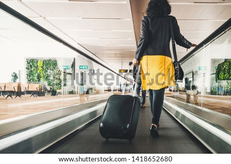 Woman traveller with travel suitcase or luggage walking in airport terminal walkway for vacation travel abroad. concept of travel around world, tourism. Brunette in yellow skirt goes on escalator. #1418652680
