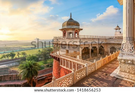 Agra Fort - Medieval Indian fort made of red sandstone and marble with view of dome at sunrise. View of Taj Mahal at a distance as seen from Agra Fort. #1418656253