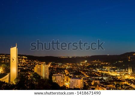 Germany, Stuttgart, Starry sky full of stars over skyline of houses of stuttgart city from above by night in summertime #1418671490