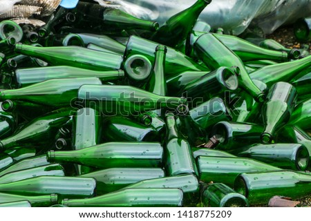 whole and broken green bottles, lie a mountain on the pavement. Concept: waste recycling, disposal of garbage and glass objects. #1418775209