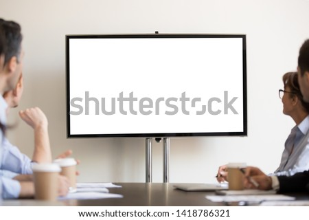 Focused business people gather at boardroom sitting at desk looking at tv white mock up with copyspace blank screen for advertisement. Seminar, presentation, corporate team at company training concept