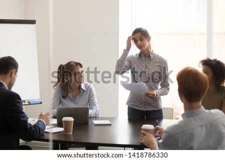 Nervous indian female worker presenter speaker feels embarrassed and shy stands in front of multi-ethnic colleagues clients at conference business meeting, timid stressed not prepared employee concept #1418786330