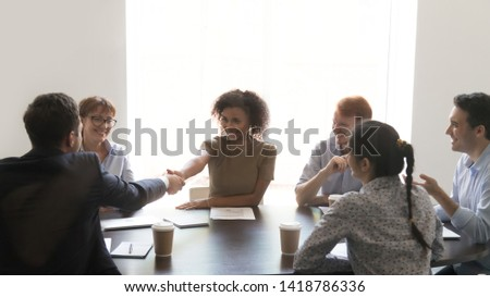 Mixed race female boss team leader shake hands greeting corporate client diverse people gather in office conference room for negotiation planning future collaboration make important decision concept #1418786336