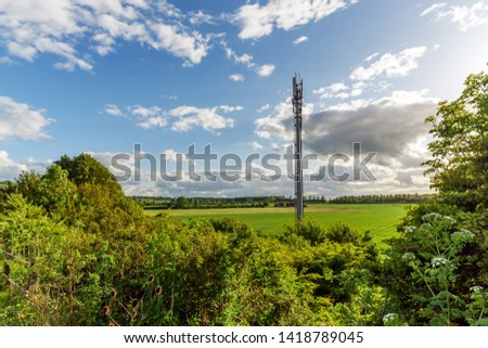 Sunset view British Mobile Operator Mast over field Royalty-Free Stock Photo #1418789045