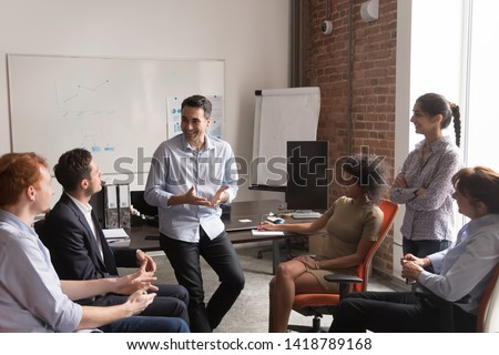 Multi racial businesspeople gather at briefing, positive team leader talking to office employees interns or students at corporate training teach explain project strategy discuss business plan concept #1418789168