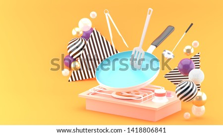 The pan is cooking, surrounded by colorful balls on an orange background.-3d rendering.