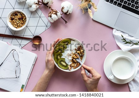 Female hand hold spoon over healthy breakfast concept bowl enjoy detox morning meal on work table background with laptop milk, woman eat natural granola nutrition detox food in home office, top view #1418840021
