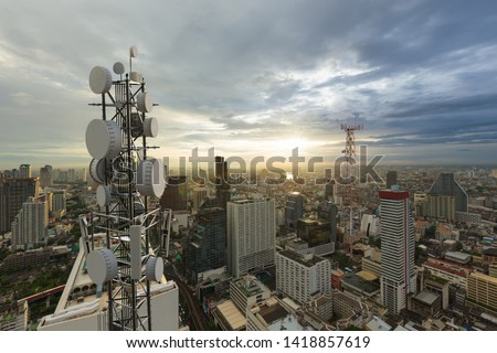 Telecommunication tower with 5G cellular network antenna on city background Royalty-Free Stock Photo #1418857619