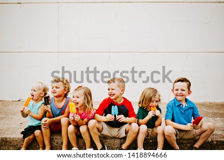 Group of Kids Eating Colorful Frozen Popsicles in the Summer #1418894666