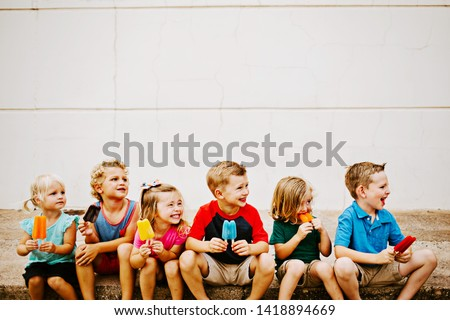 Group of Kids Eating Colorful Frozen Popsicles in the Summer #1418894669