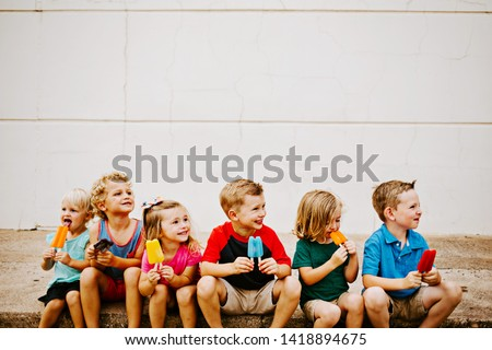 Group of Kids Eating Colorful Frozen Popsicles in the Summer #1418894675
