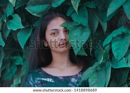 A beautiful girl standing in between leaves. #1418898689
