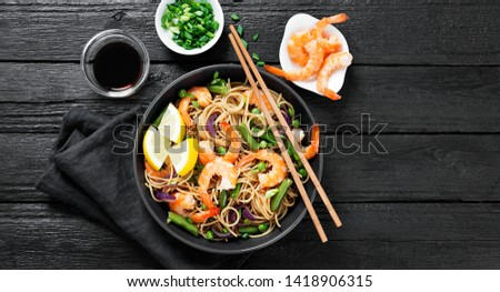 Stir fry noodles with shrimps and vegetables in black bowl. #1418906315