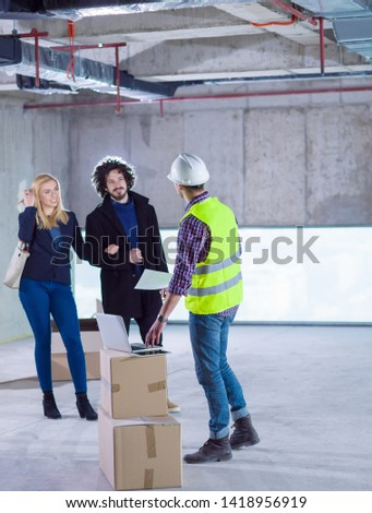 worker using laptop computer while showing house design plans to a young couple at construction site #1418956919