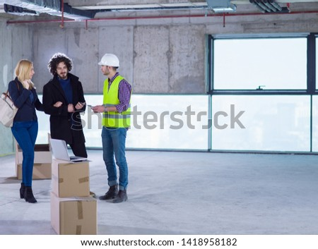 worker using laptop computer while showing house design plans to a young couple at construction site #1418958182
