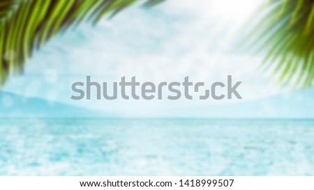 Blurred summer natural marine tropical blue background with palm leaves and sunbeams of light. Sea and sky with white clouds. Copy space, summer vacation concept #1418999507