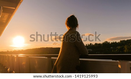 Woman standing on deck of cruise ship and looking at landscape. Sunset light, golden hour. Nature and journey concept #1419125993