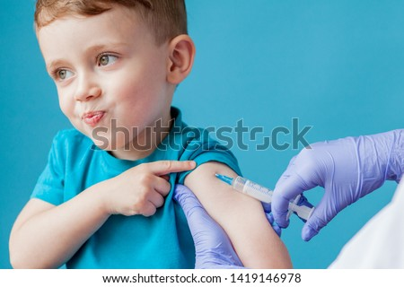 Vaccination concept. Female doctor vaccinating cute little boy on blue background, closeup. #1419146978