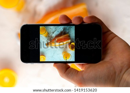 top view of hand holding a phone doing a mobile food photography