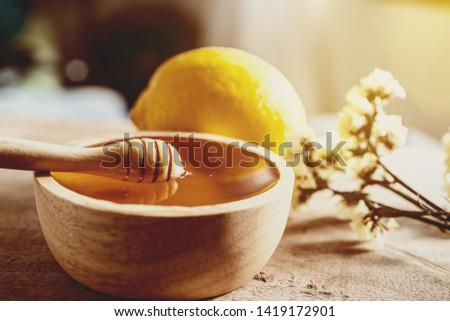 Healthy organic scoop Thick honey dipping with wooden honey spoon from a wooden bowl, honey dripping, pouring honey into the bowl. Close-up. #1419172901