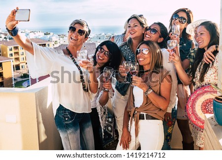 Happy group of females together in friendship on the terrace.Celebrating a birthday with large smiles and red wine glasses. One selfie for the missing friends #1419214712